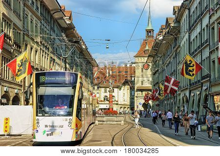 Running Tram And People At Piper Fountain On Spitalgasse Bern