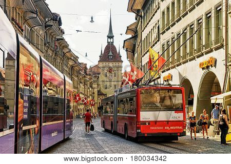 Running Trams And People At Kafigturm Tower On Marktgasse Bern