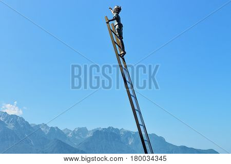 Montreux Switzerland - August 27 2016: Sculpture with a boy on the ladder on Geneva Lake embankment in Montreux Vaud canton Switzerland