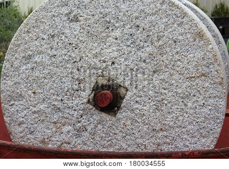 Upclose view of large millstone wheel with textured surface and a reddish brown metal hub resting inside a reddish brown metal bowl
