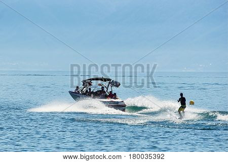 Motorboat With Man Wakeboarding In Lake Geneva In Lausanne