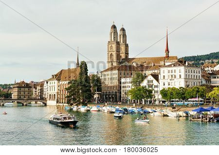 River boat at Limmat Quay and Grossmunster Church in Zurich Switzerland. People on the background poster