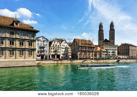 River Cruiser At Limmat River And Grossmunster Church In Zurich