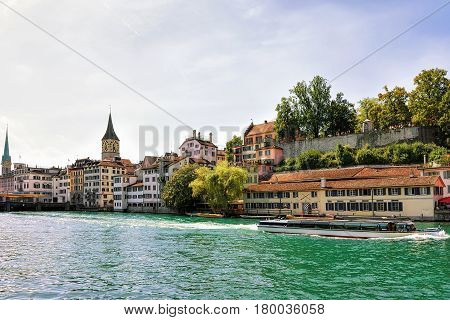 River cruiser at Limmat quay and St Peter Church and Fraumunster Church in the city center of Zurich Switzerland.