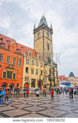 Tourists With Umbrellas Near Old Town Hall In Prague