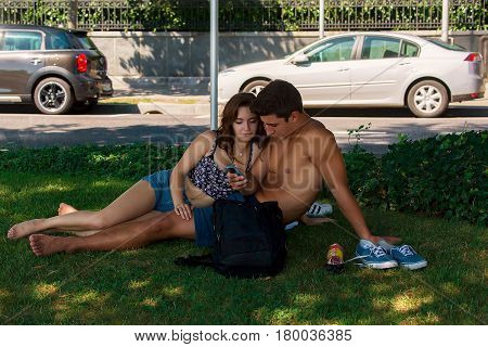 Young Couple Sitting In Lawn In Park Of Lausanne