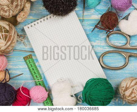 Open the notebook and set for needlework on a blue wooden table. The concept of home handicraft.