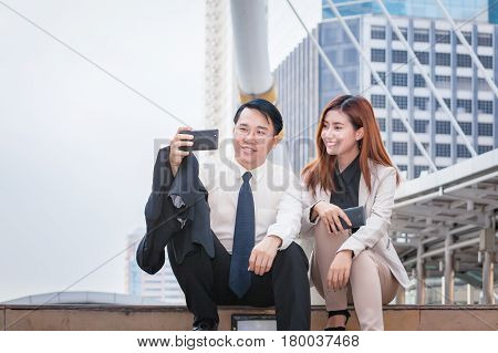 businessman sitting and using phone to take photo as selfie with colleague together and modern office building background