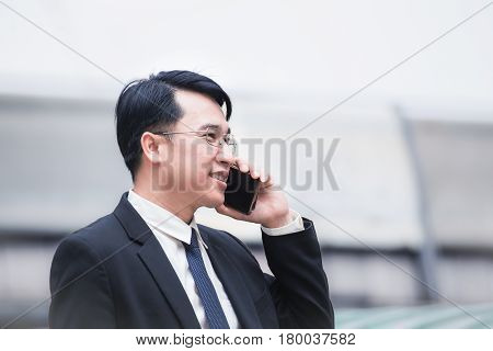 Businessman Using A Cell Phone And Modern Office Building Background