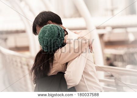 Asian happy woman wearing yarn hat meet and hugging with boyfriend together at the street wedding theme background