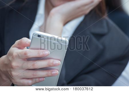 businesswoman using a cell phone and modern office building background