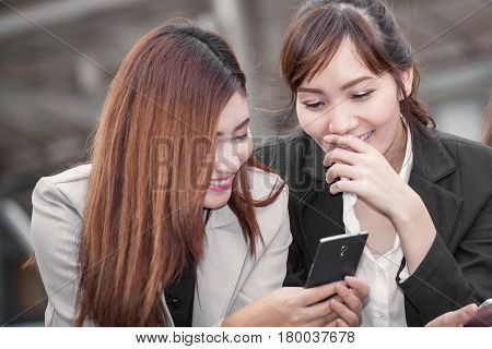 Asian business woman happy to use cell phone with colleague and discussion topic on business conceptual