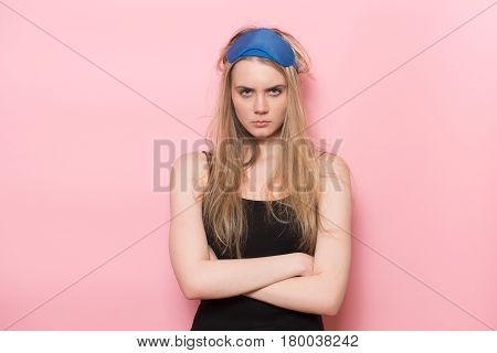 Angry sad sleepy woman just woke up and standing unhappy with arms crossed wearing sleeping mask.
