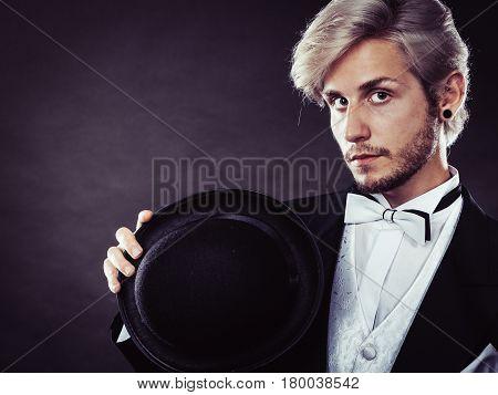 Tuxedo male fashion classical look concept. Elegantly dressed blonde man holding black fedora hat. Studio shot on dark background