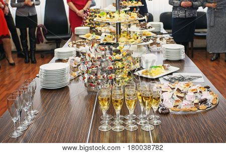 Fancy served fruit buffet on luxurious party table in restaurant. corporate event or wedding celebration. glasses of champagne