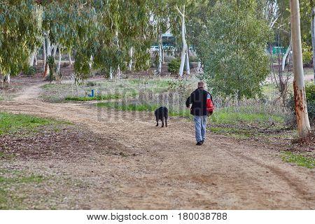 Ganey Aviv - 02 December 2016: A Man Walks With His Dog In The Field, Near Ganey Aviv, Israel