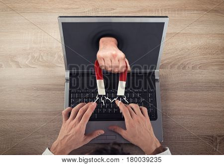 Magnet attracts a man to a computer. Capturing people with marketing