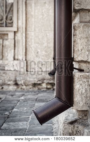 Brown metal drainpipe on the corner of a stone house