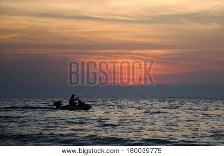 silhouette people on jetski in sunset time