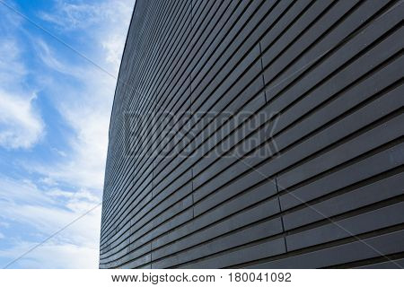 Dark wooden wall diminishing perspective into light cirrus clouded blue sky
