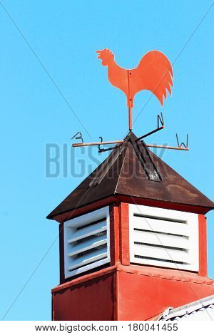 Close up image of a red Weather Vane against blue sky