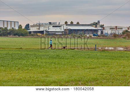Ganey Aviv - 02 December 2016: Three Friends Walk With Dogs In The Field, Near Ganey Aviv, Israel