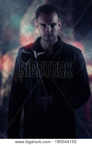 Man wearing a black leather jacket holding an axe in the rain. Book cover design