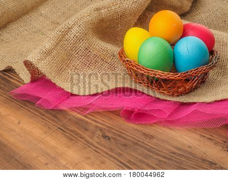 Easter colored egg in a wicker-work from withe basket, burlap and a red grid on a brown background from old wood, rural table. Russian and Ukrainian, orthodox, slavic traditional Easte.