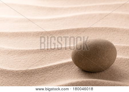 Round stone on beach sand. Zen meditation cocept for relaxating and concentration or spa wellness theme for purity and balance. Background with copy space.