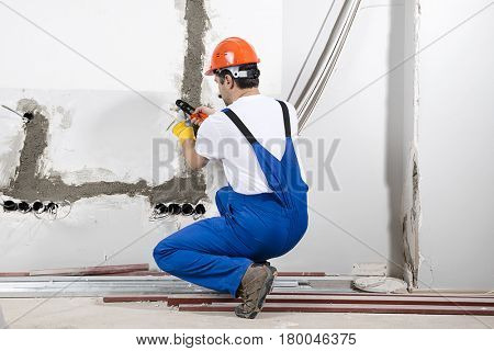 Electrician wearing bib overalls and helmet installing electricity cables.