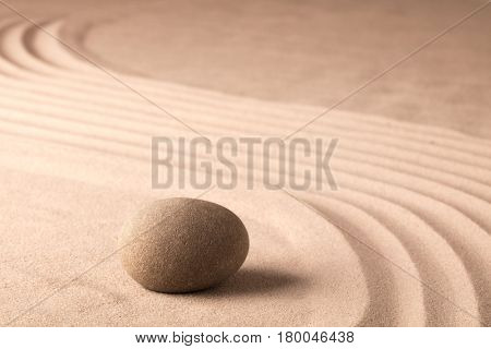 Stone in zen meditation garden. Texture sand background.