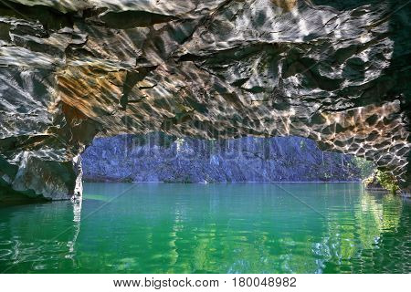 Glare of sun from water on walls of cave in marble quarry in Ruskeala, Karelia, Russia