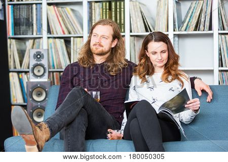 a couple relaxing toghether on a couch, reading and listening to music