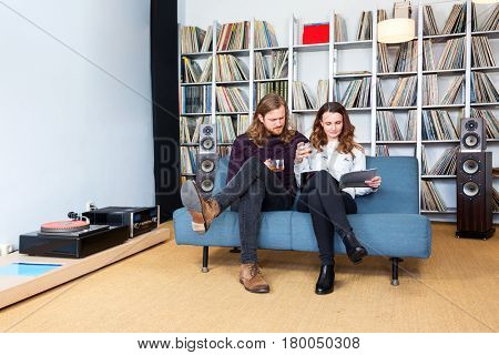 a couple sitting on the sofa reading a magazine together while listening to music