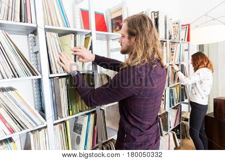 a couple browsing through racks of vinyl records in their lp collection