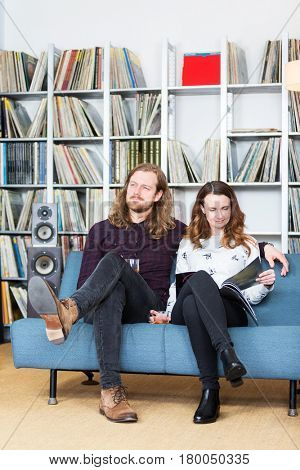 a couple relaxing toghether on a couch reading and listening to music