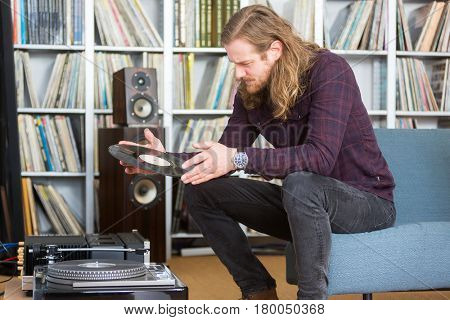 long haired man looking at the track list on a vinyl long playing record to put on the turntable