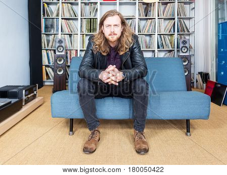 long haired man seriously listening to music
