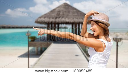 summer holidays, travel, people and vacation concept - happy young woman in hat pointing finger over exotic tropical beach with bungalow and sea shore background