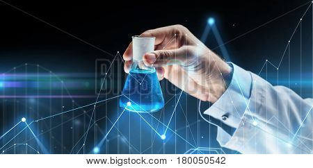 science, chemistry, research and people concept - close up of scientist hand holding test flask with chemical and virtual charts over dark background