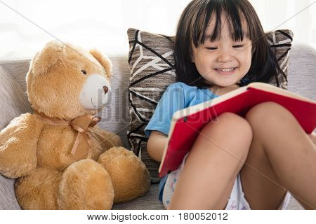 Smiling Asian Chinese Little Girl Reading Book With Teddy Bear