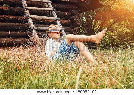 Boy lies near old barn in the garden
