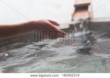 check the temperature by using hand at the hot spring pool