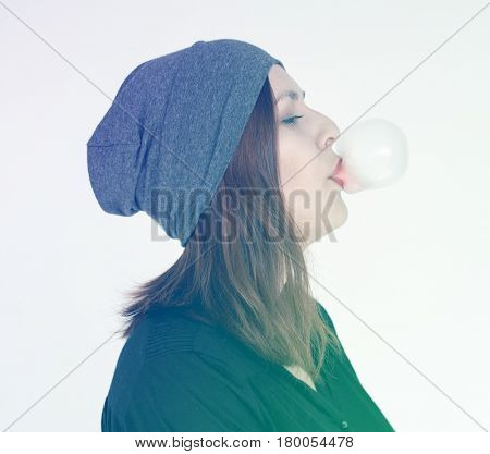 Woman eating and blowing bubblegum on white background