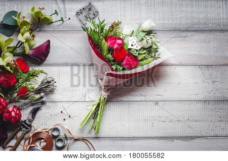 Bouquet of red and white roses, love, callas, carnations and ribbons on the wooden table