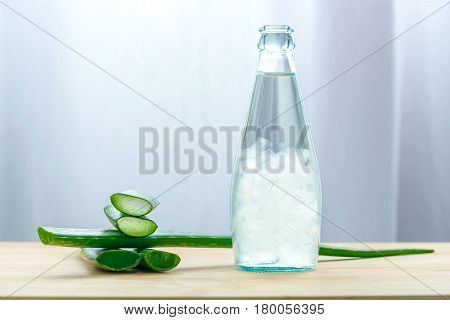 Aloe vera juice in bottle with fresh aloe vera leaves on wooden background