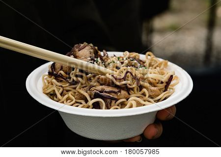 Midsection Of Woman Holding Street Food with noodles and meat. Focus on foreground