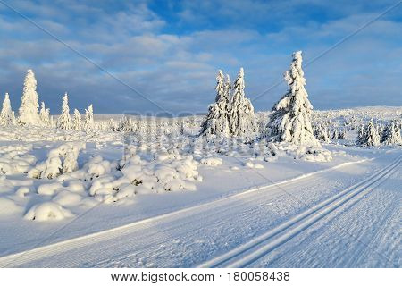 Snowy road and mountains heavily covered with fresh snow against the blue sky and clouds. Subpolar Urals, Russia