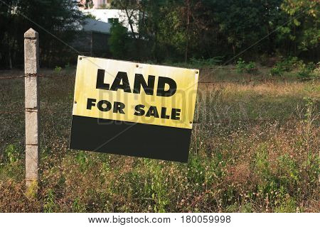 Yellow signboard with Land For Sale iscription outdoor