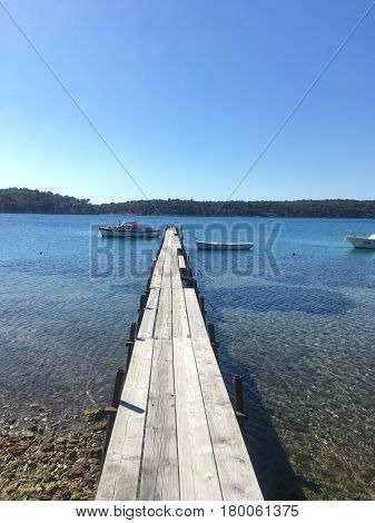 Wooden jetty leading into sea on Rab island, Croatia.